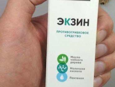 Коробка препарата Экзин против грибка в руке мужчины.